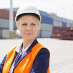 Beautiful female engineer looking away in shipping yard